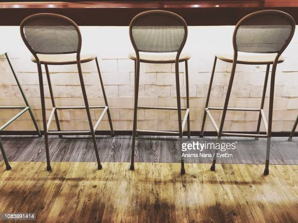 Empty Chairs By Tables On Hardwood Floor