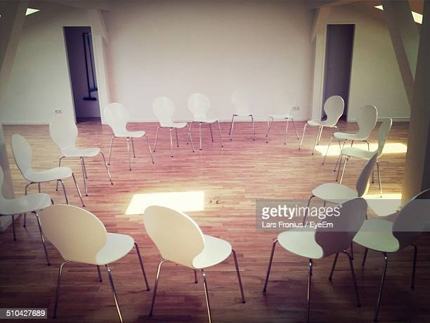 Empty chairs in a circle on hardwood floor