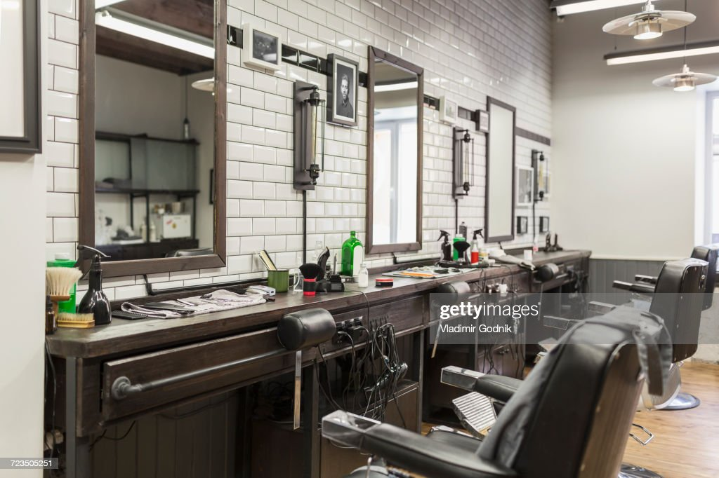 Empty chairs in front of mirrors at barber shop : Stock Photo
