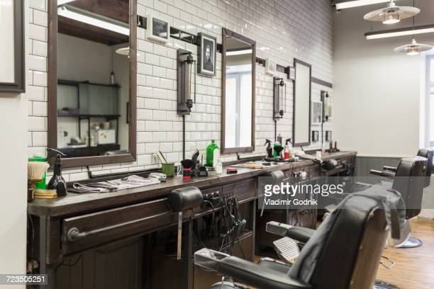 empty chairs in front of mirrors at barber shop - barber shop stock photos and pictures