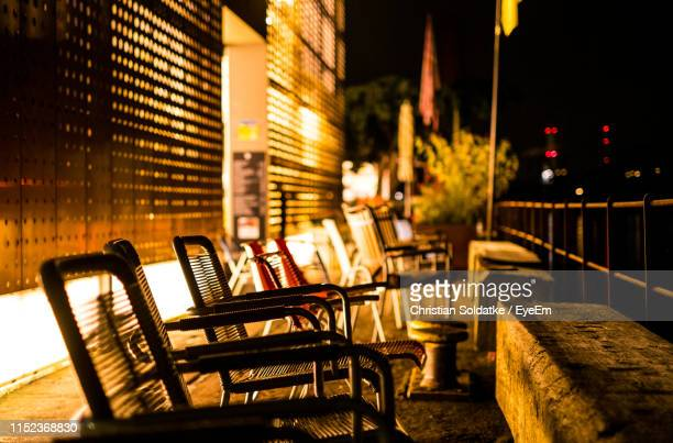 empty chairs in row at night - christian soldatke stock pictures, royalty-free photos & images