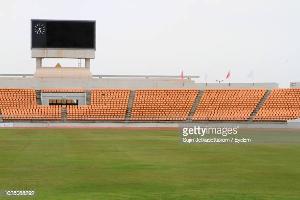 empty chairs in stadium against sky - empty stadium stock pictures, royalty-free photos & images