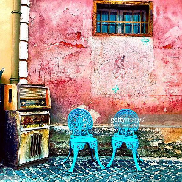 Empty Chairs On Footpath By Old House