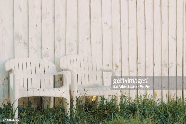 Empty Chairs On Grass Against Wooden Wall