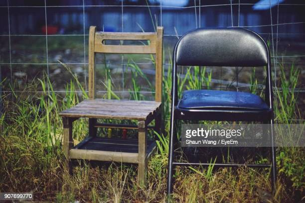 Empty Chairs On Grassy Field