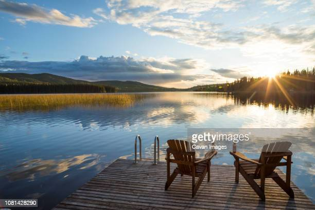 empty chairs on wooden pier over lake against cloudy sky during sunset - kamloops stock pictures, royalty-free photos & images