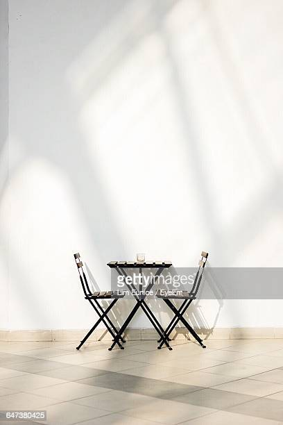 Empty Chairs With Table Against White Wall