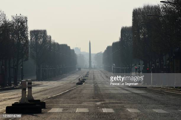 Empty Champs Elysees avenue is pictured on March 28, 2020 in Paris, France. The country has introduced fines for people caught violating its...