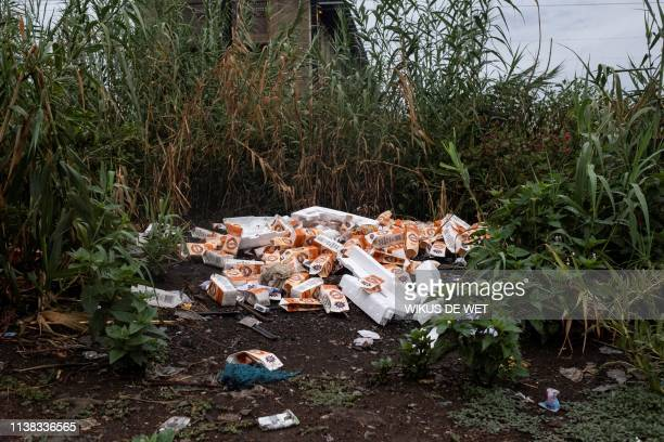 Empty Chibuku beer cartons are seen lying in a field on April 5 2019 in Kliptown near Soweto South Africa goes to the polls next month the country's...