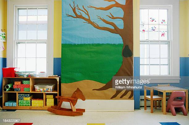 Empty childcare room with toys and blocks and a construction paper tree on the wall