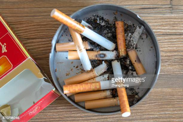 Empty cigarette box cigarette butts and ashtray arranged for photography China is the world's largest producer and consumer of tobacco and 44% of the...