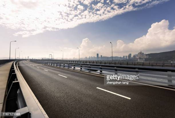 empty city road of cross-sea bridge with cityscape background - freie straße stock-fotos und bilder