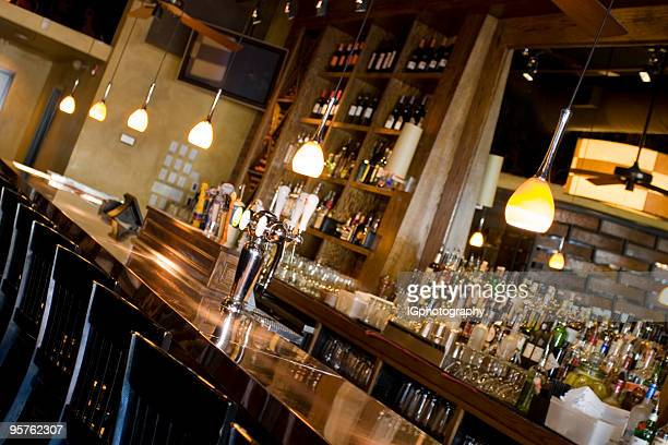 Empty Classy Bar with Alcohol Bottles, Barstools and Mirror
