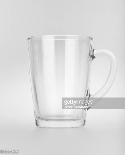 empty clear glass mug with reflections, isolated on white background - glas materiaal stockfoto's en -beelden