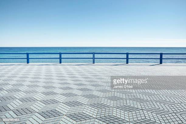 empty coastal boardwalk with geometric tile pattern, alicante, spain - boardwalk stock pictures, royalty-free photos & images