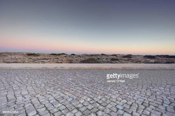 empty cobbled road at dawn, portugal - 玉石 ストックフォトと画像
