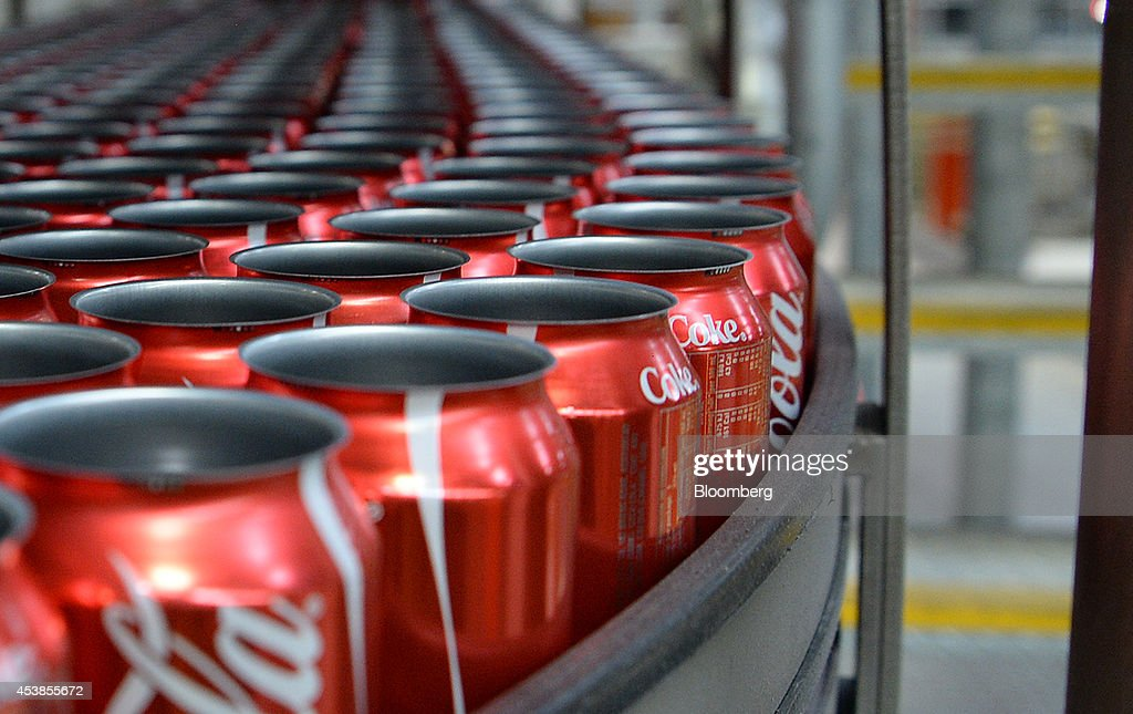 Empty Coca-Cola Classic cans move along a conveyor to be filled and sealed at a Coca-Cola Amatil Ltd. production facility in Melbourne, Australia, on Tuesday, Aug. 19, 2014. Coca-Cola Amatil flagged a second consecutive drop in full-year earnings amid weak consumer confidence and rising costs in Indonesia. Photographer: Carla Gottgens/Bloomberg via Getty Images