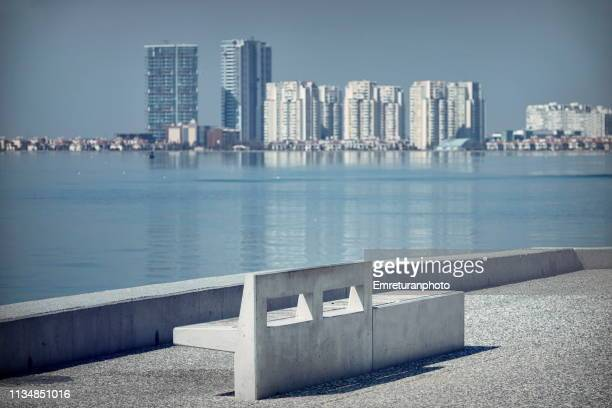 empty concrete bench on the seafront with apartment blocks at the background. - emreturanphoto stock-fotos und bilder