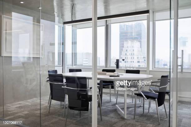 leerer konferenzraum gegen fenster im büro - konferenzraum stock-fotos und bilder