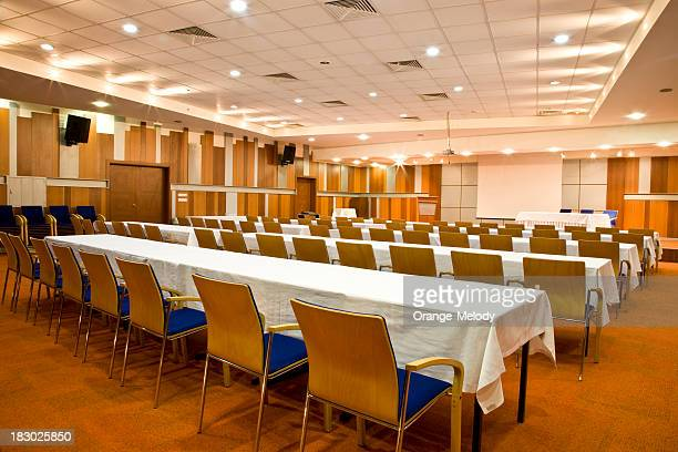 Empty conference room with rows of tables and chairs