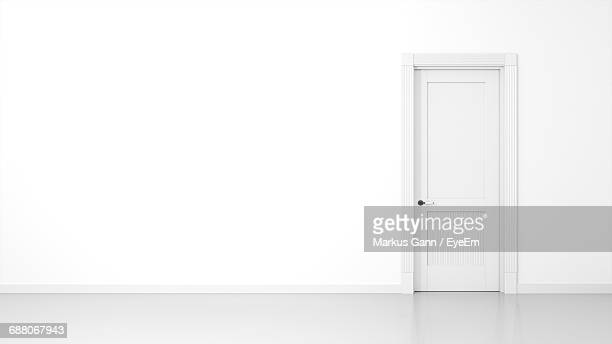 empty corridor by closed door on white wall - deur stockfoto's en -beelden