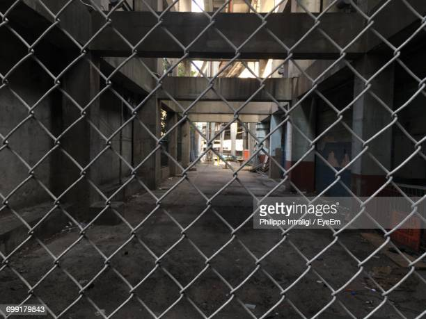 Empty Corridor Of Building Seen Through Chainlink Fence