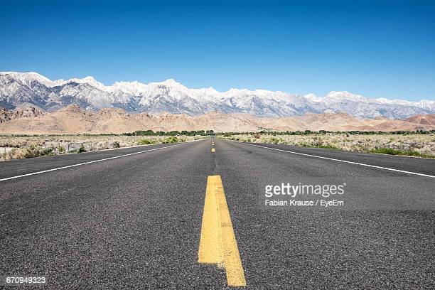 Empty Country Road Against Snowcapped Mountains