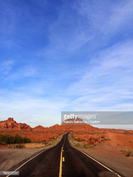 Empty Country Road Amidst Rock Formations Against Sky