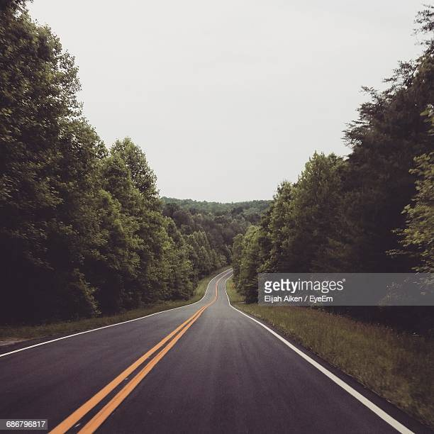 empty country road amidst trees against sky - double yellow line stock photos and pictures