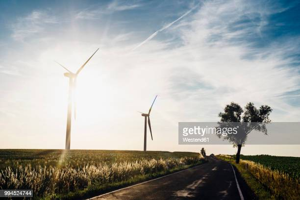 empty country road and wind turbines at sunset - gegenlicht stock-fotos und bilder