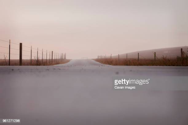 empty country road by fence against clear sky during sunset - sonoma county stock pictures, royalty-free photos & images