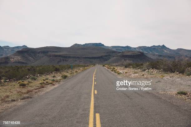 empty country road passing through arid landscape against sky - double yellow line stock photos and pictures
