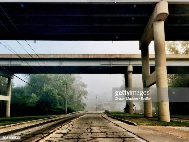 empty cracked road below bridges during foggy weather - empty road stock pictures, royalty-free photos & images