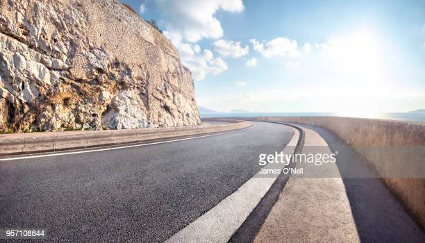 empty curved coastal road on sunny day - winding road stock pictures, royalty-free photos & images