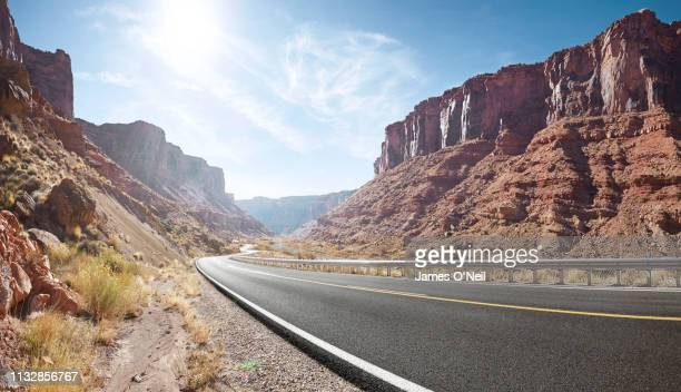 empty curved road in sandstone cliff valley - two lane highway stock pictures, royalty-free photos & images