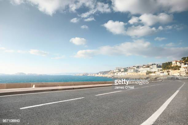 empty curved road with background sea and city - route photos et images de collection