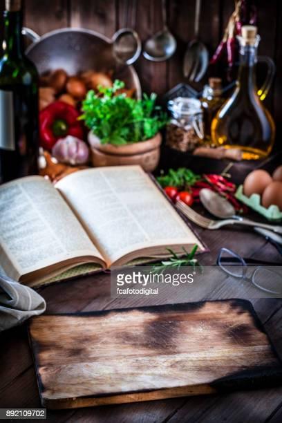 leere schneidebrett mit einem alten kochbuch auf rustikalen küchentisch - kochbuch stock-fotos und bilder