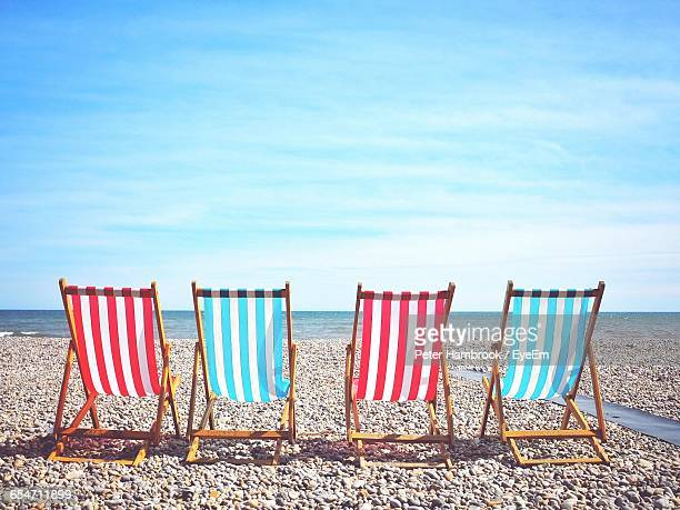 empty deck chairs at beach against sky - southwest england stock photos and pictures