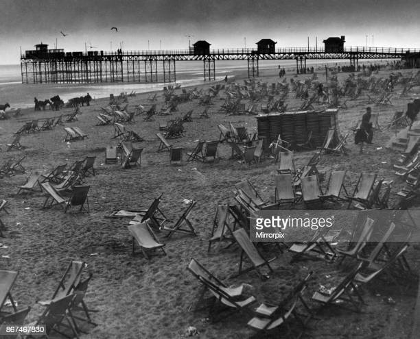 Empty deck chairs sprawl forlornly on the deserted beach at Rhyl after the storm had driven home the holidaymakers 26th May 1955
