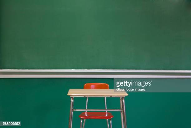 empty desk by classroom chalkboard - education stock pictures, royalty-free photos & images