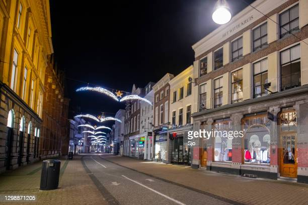 empty diezestraat shopping street in the city center of zwolle at night. - curfew stock pictures, royalty-free photos & images