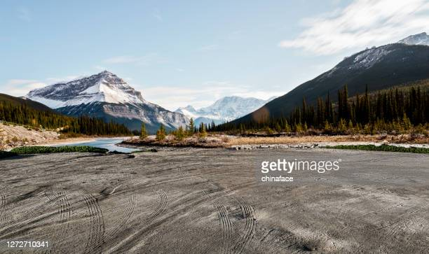 empty dirt beach with traces against canadian rockies - hill stock pictures, royalty-free photos & images
