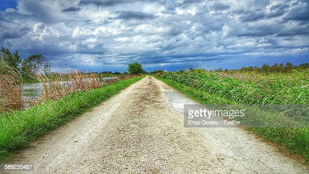 Empty Dirt Road Against Cloudy Sky