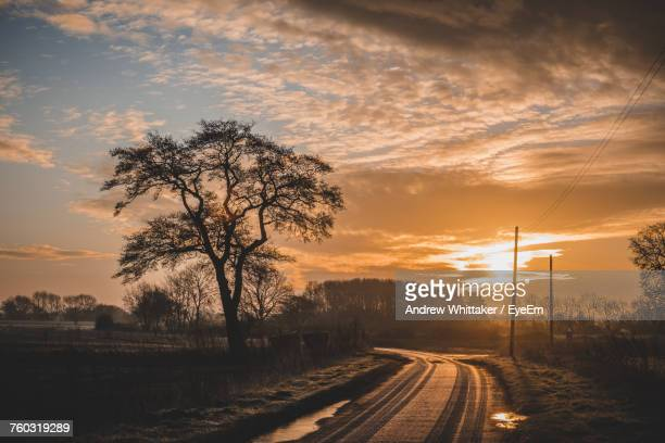 Empty Dirt Road By Silhouette Bare Trees Against Cloudy Sky