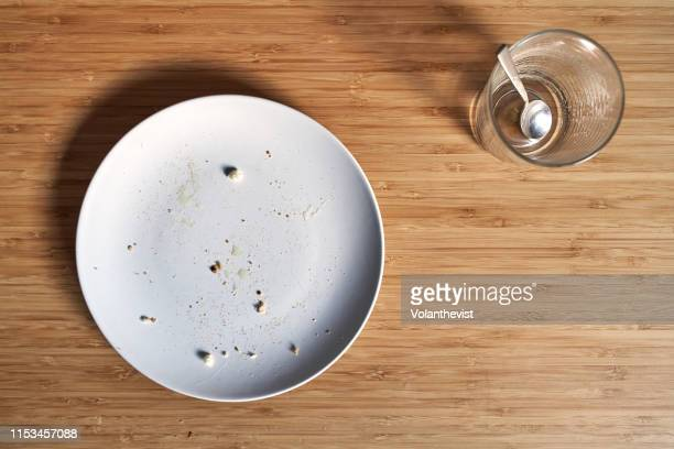 empty dish with bread crumbs and empty cup of coffee on a bamboo wooden table - beenden stock-fotos und bilder
