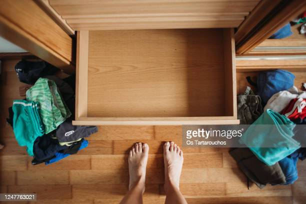 empty dresser drawer and messy clothes all over the floor before organizing - drawer stock pictures, royalty-free photos & images