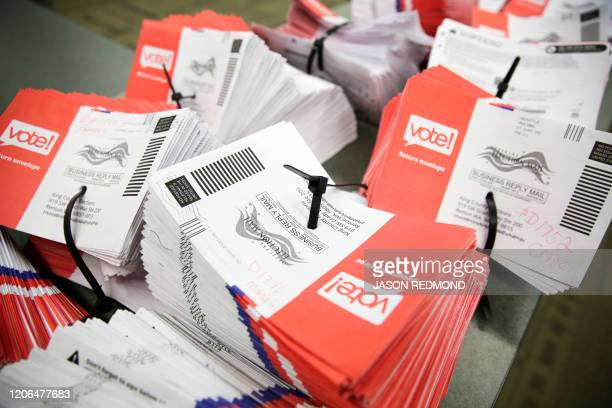 Empty envelopes of opened vote-by-mail ballots for the presidential primary are stacked on a table at King County Elections in Renton, Washington on...