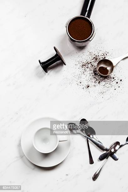 empty espresso cup, spoons and pressurized portafilter on white marble - ground coffee stock photos and pictures