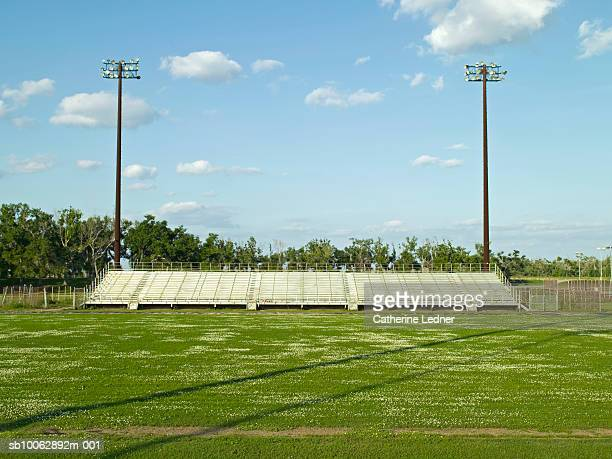 empty football field, seats and lights in background - empty bleachers stock photos and pictures