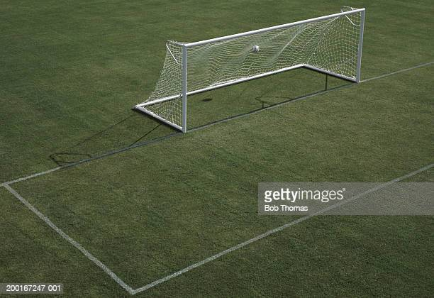 Empty football pitch, ball in goal, elevated view